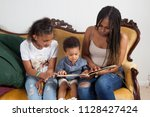 black mother reading to her... | Shutterstock . vector #1128427424