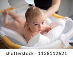 mother bathing her son in white ... | Shutterstock . vector #1128512621