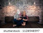 unusual couple reading a book...   Shutterstock . vector #1128548597