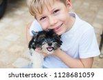 happy caucasian boy lovingly... | Shutterstock . vector #1128681059