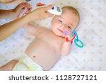 mother measuring temperature of ... | Shutterstock . vector #1128727121