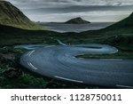 a curvy road down a green hill... | Shutterstock . vector #1128750011