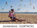 Small photo of mother and son sitting on the beach and flying around the birds seagulls