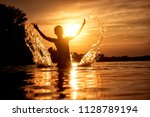 boy in the water on the sunset... | Shutterstock . vector #1128789194
