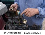man working on car light in... | Shutterstock . vector #1128885227
