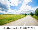 an asphalt road through the... | Shutterstock . vector #1128993281