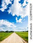 a view of a dirt road through... | Shutterstock . vector #1128993329