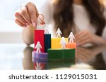 businesswoman's hand placing... | Shutterstock . vector #1129015031