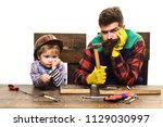 father and son in workshop.... | Shutterstock . vector #1129030997
