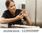 happy female confectioner... | Shutterstock . vector #1129055009