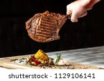a large roasted piece of mutton ... | Shutterstock . vector #1129106141