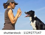 owner commands her dog  border... | Shutterstock . vector #1129277147