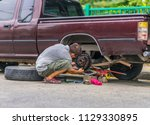 man doing roadside repairs on a ... | Shutterstock . vector #1129330895