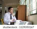 handsome asian student reading... | Shutterstock . vector #1129353167