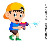 boy playing with water gun | Shutterstock . vector #1129364174