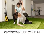 physical therapist assisting... | Shutterstock . vector #1129404161