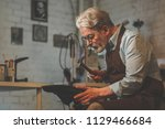 an elderly man at work in a... | Shutterstock . vector #1129466684