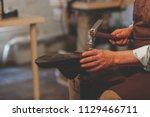 an elderly shoemaker at work... | Shutterstock . vector #1129466711