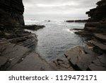 brown cliffs of a rocky coast... | Shutterstock . vector #1129472171