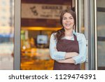 smiling woman in an apron in... | Shutterstock . vector #1129474391