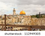 Two of Islam and Judaism's holiest sites, Jerusalem's Dome of the Rock and the Western Wall, seen through barbed wire. Israel - stock photo
