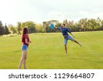 couple in love playing frisbee... | Shutterstock . vector #1129664807