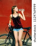 a girl with a bicycle drinks... | Shutterstock . vector #1129769999