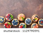 delicious berry tartlets or... | Shutterstock . vector #1129790591