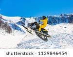 racer on a snowcat in flight ... | Shutterstock . vector #1129846454