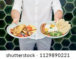 man holding two plates with... | Shutterstock . vector #1129890221