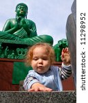 Small photo of baby playing in front of large Buddha statue in Tagata Temple, Nagoya, Japan