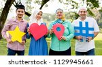 muslim family holding up... | Shutterstock . vector #1129945661