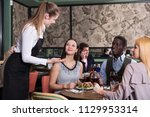 hospitable young waitress... | Shutterstock . vector #1129953314