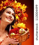 Girl with wreath of autumn leaves holding basket with fruit. - stock photo