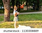 schoolgirl in uniform eating an ... | Shutterstock . vector #1130308889