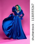 Small photo of beautiful drag queen on a pink background in a blue dress and blue hair