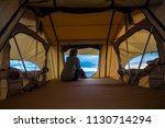 lonely independent strong middle age woman feeling the nature outdoor in a roof tent on the car. travel and lifestyle wanderlust concept for beautiful caucasian lady sitting in front of the ocean - stock photo