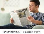 handsome man reading newspaper... | Shutterstock . vector #1130844494