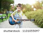 child boy playing on guitar in... | Shutterstock . vector #1131055097