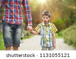 father holding hand with son in ... | Shutterstock . vector #1131055121
