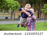 father raise up his son in a... | Shutterstock . vector #1131055127