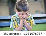 sad child boy sitting on a bench | Shutterstock . vector #1131076787