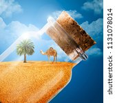 a camel and a palm tree in a... | Shutterstock . vector #1131078014