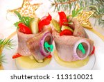 appetizer of rolled herring fillets filled with red pepper and pickles on potato ring for christmas - stock photo