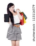 Beautiful asian woman showing empty screen of computer tablet while carrying shopping bags - stock photo