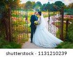 romantic kiss of newlyweds near ... | Shutterstock . vector #1131210239