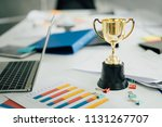 champion golden trophy on table.... | Shutterstock . vector #1131267707