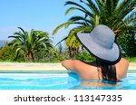 Beautiful woman enjoying sun at swimming pool - stock photo