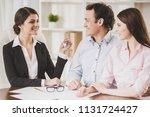 smiling realtor in black suit... | Shutterstock . vector #1131724427