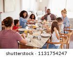 two families enjoying meal at... | Shutterstock . vector #1131754247